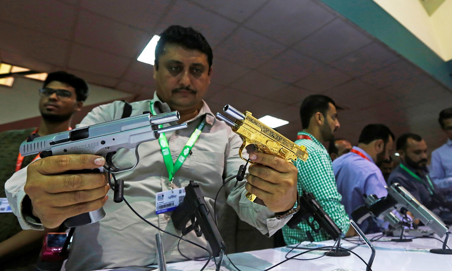 A visitor compares pistols during IDEAS-2016. ─Reuters