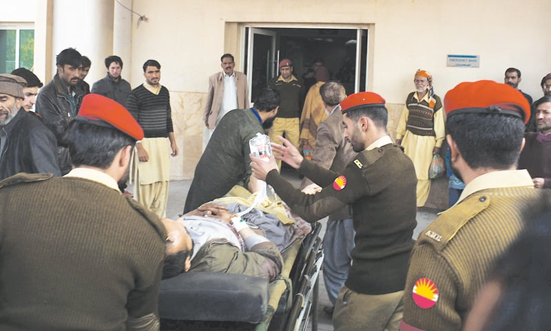 MUZAFFARABAD: Soldiers shift an injured passenger of a bus hit by Indian troops' shelling on Wednesday to a military hospital.—AFP