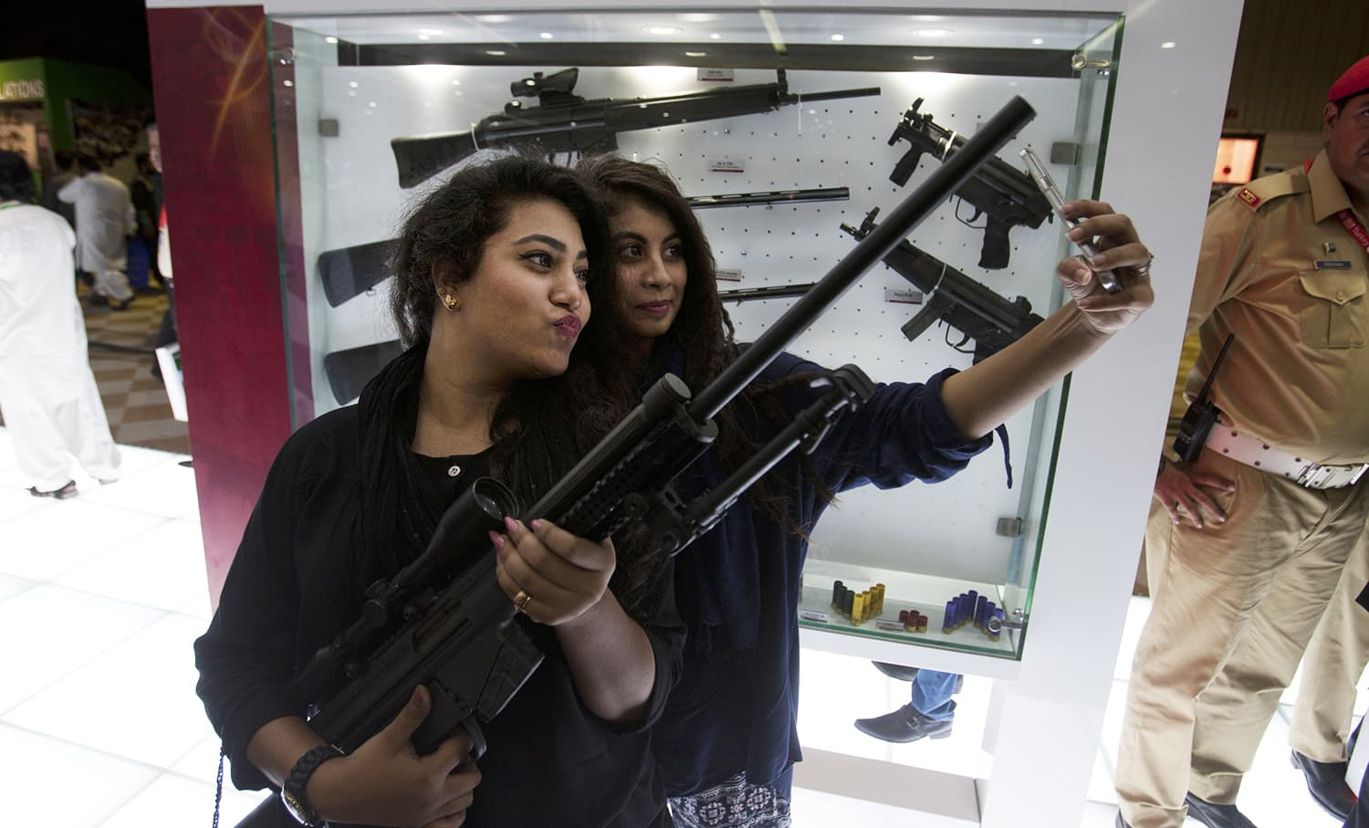 Girls take selfies holding a Pakistan-made rifle displayed at IDEAS-2016. ─AP