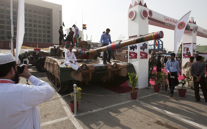 Visitors look at Pakistan made tank Al-Khalid display at the four-day IDEAS-2016. -AP