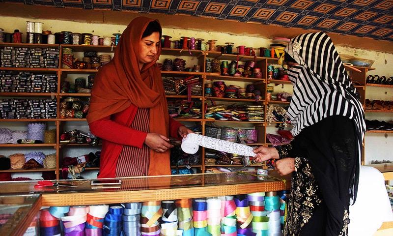 Pakistani Kashmiri woman Sara Rasheed (L) sells border trim cloth to a customer at her shop  in the women's market.— AFP