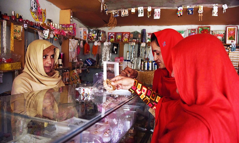 Kashmiri women select ornaments from a shop in the women's market.—AFP