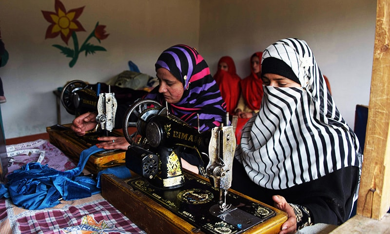 Kashmiri girls stitching cloth during their class in the women's market.—AFP