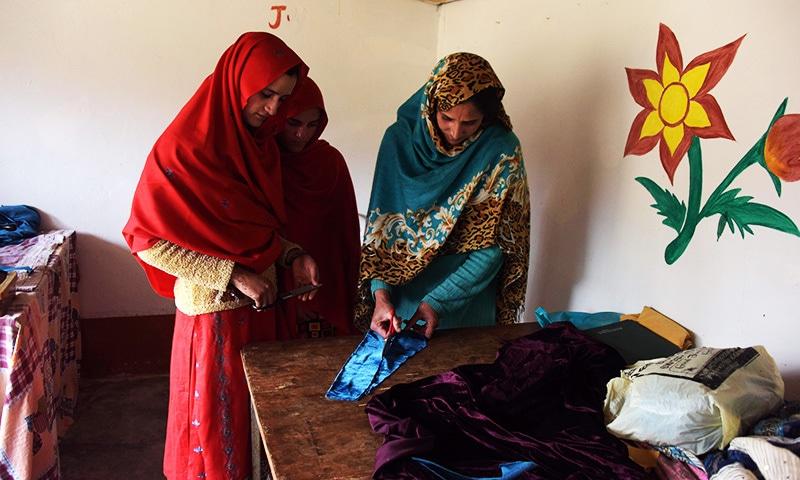 Kashmiri girls cut cloth during their class in the women's market.—AFP
