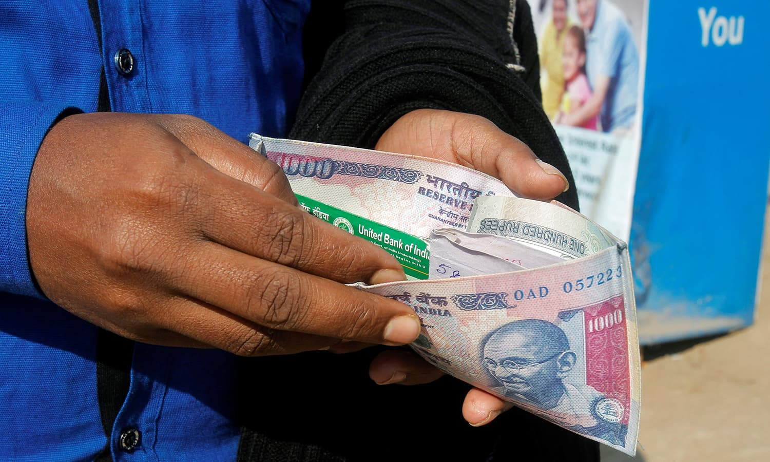 A man puts his debit card inside an Indian currency printed wallet outside a bank in Agartala, India. ─AFP