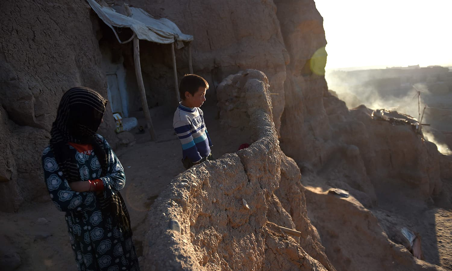Afghan Hazara children stand in front of the cave where they live with their family in Bamiyan province. ─AFP