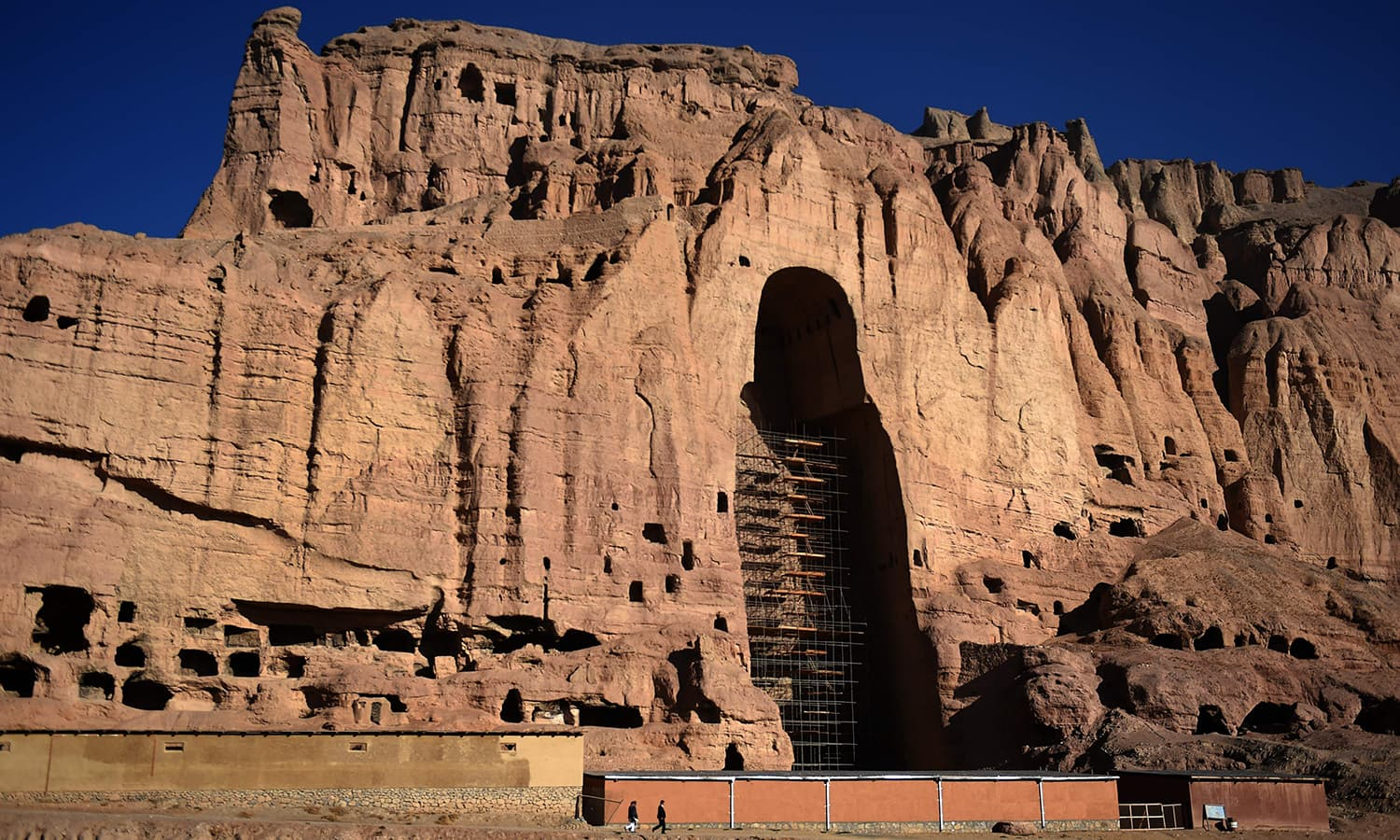 Afghan men walk at the site of the giant Buddha statues, which were destroyed by the Taliban in 2001. ─AFP