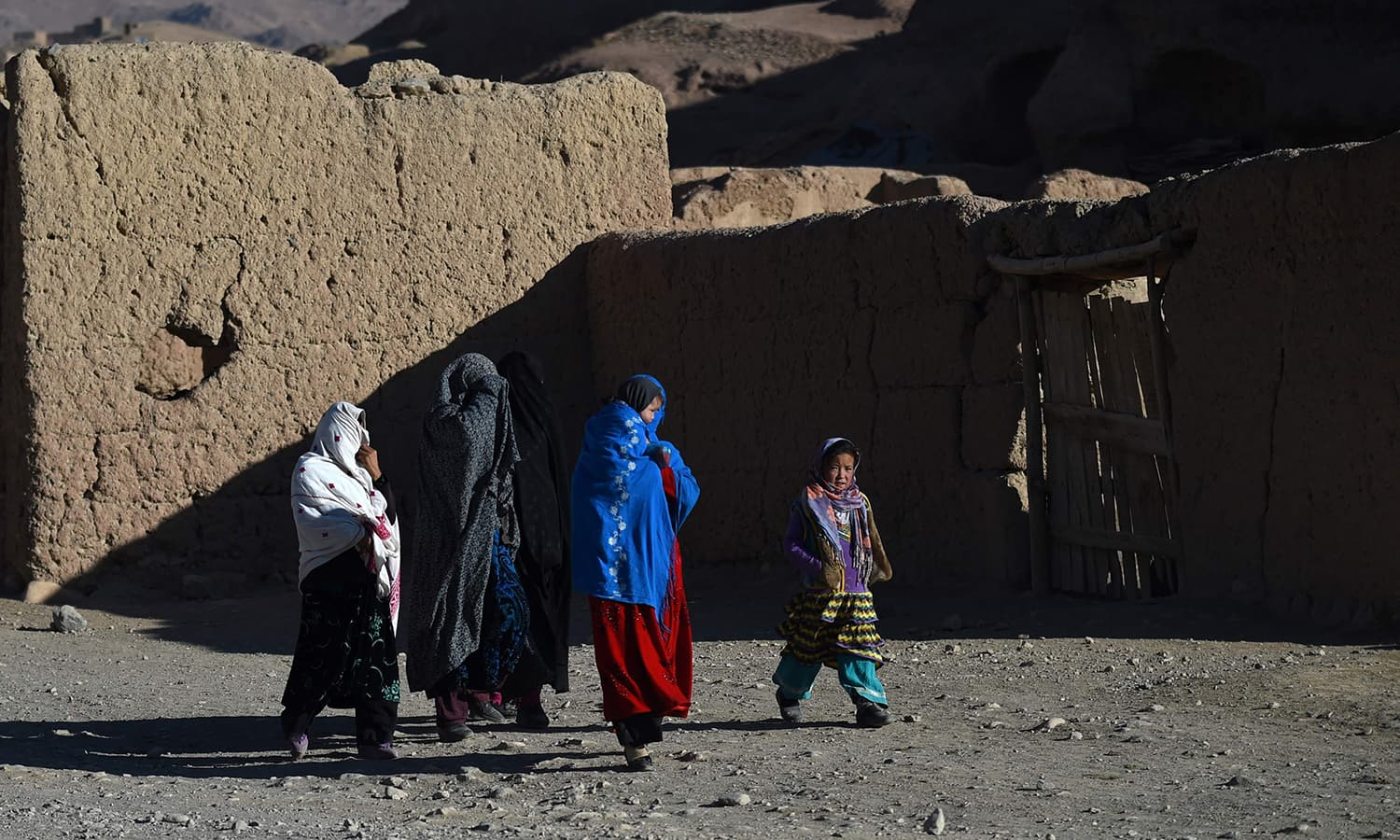 Afghan Hazara women walk along a road in Bamiyan province. ─AFP