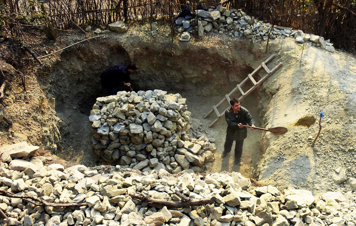 Men prepare an underground bunker in Athmuqam village at the LoC.—AFP
