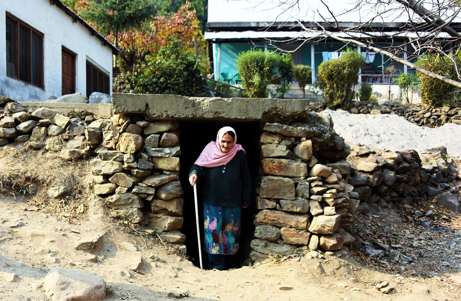 A woman walks out of an underground bunker in Athmuqam village at the LoC.—AFP