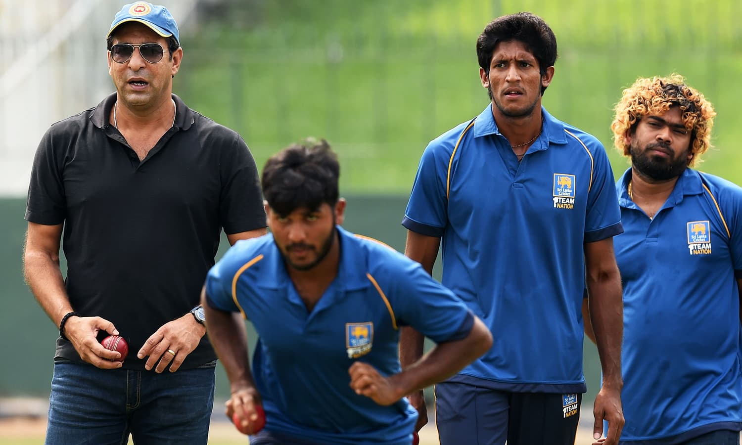 Sri Lankan cricketers Lasith Malinga and Kasun Rajitha look on during the first coaching session by Wasim Akram. -AFP