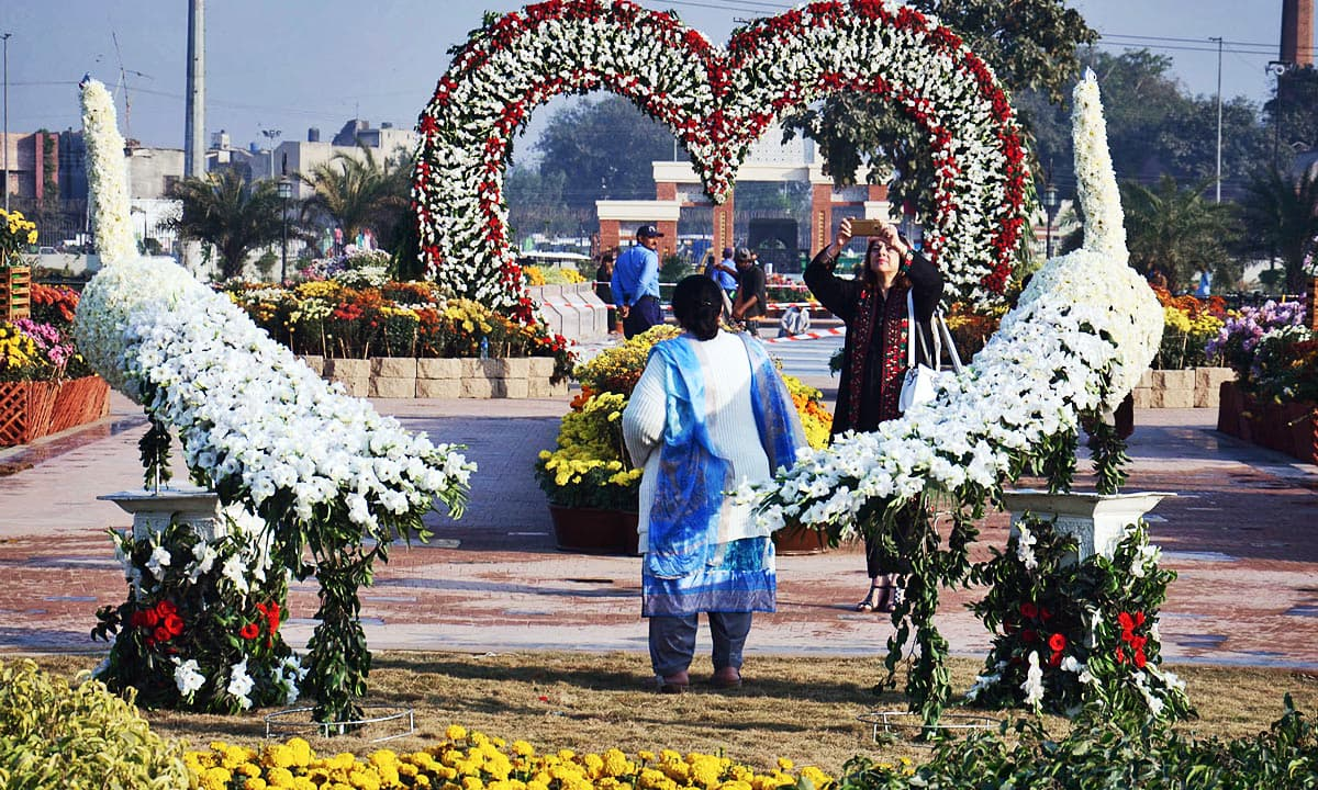 Visitors taking pictures during flowers exhibition at Greater Iqbal Park. —Online