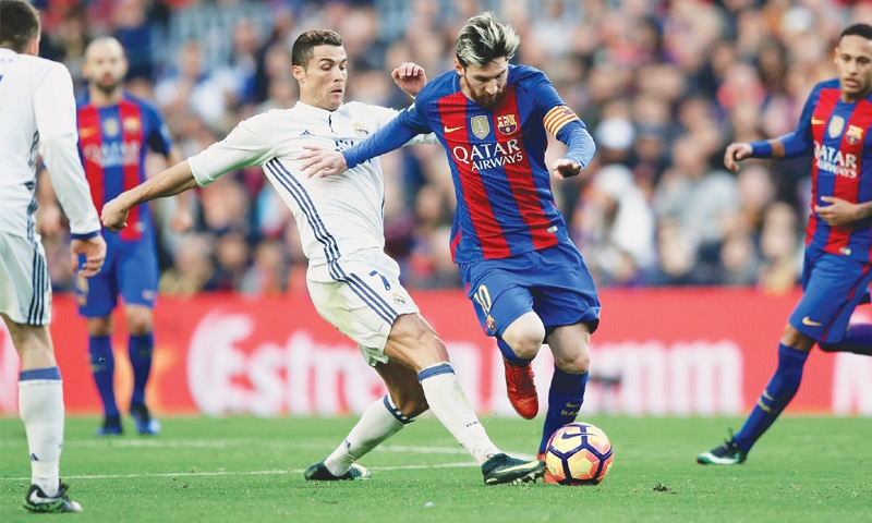 BARCELONA'S Lionel Messi goes past Real Madrid's Cristiano Ronaldo during the 'Clasico'.—AP