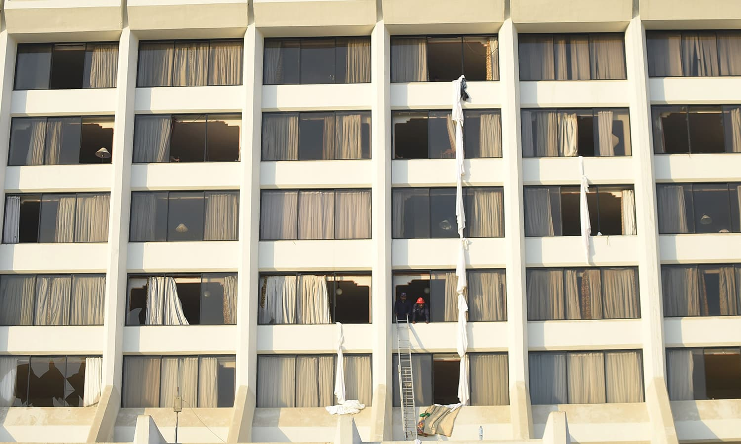 Firefighters look from a room of Regent Plaza after the fire. — AFP