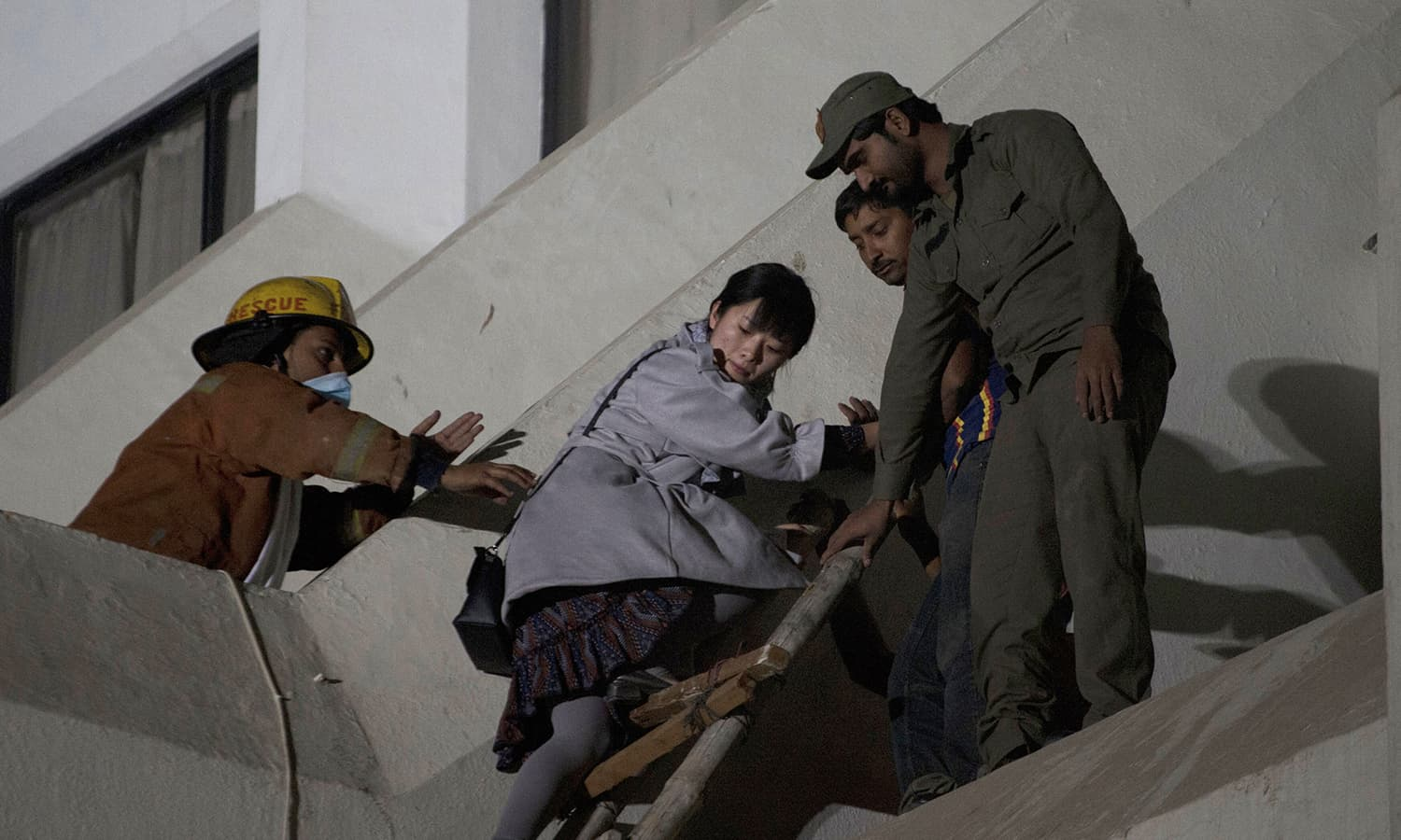 Volunteers help a foreigner in evacuating after the fire. — AFP