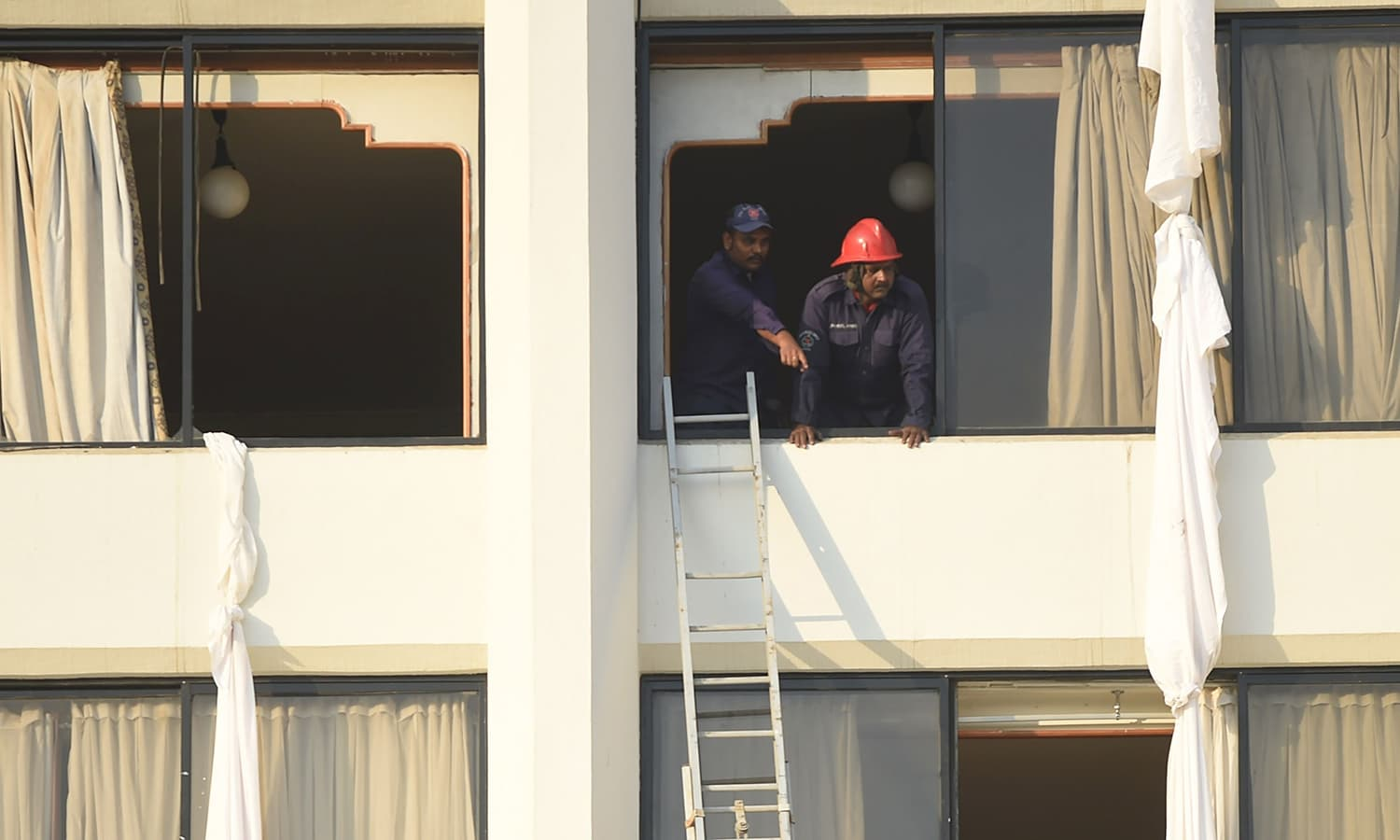 Firefighters looking outside from a room of Regent Plaza hotel. ─AFP