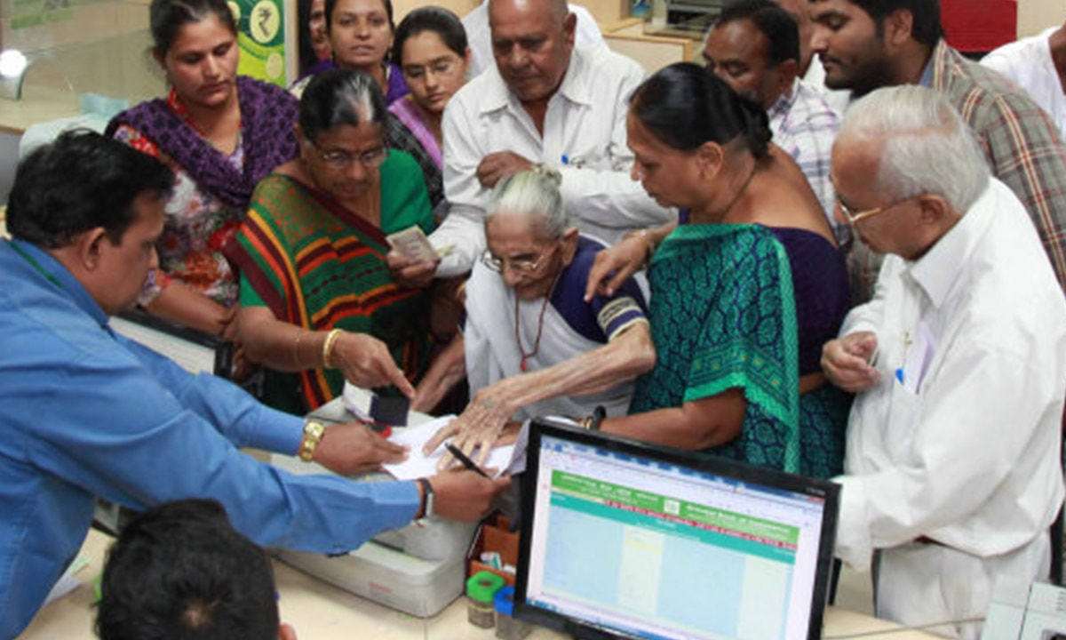 Indian Prime Minister, Narendra Modi's mother Heera Ba Modi (C) exchanges money at a bank in Rysan village | AFP