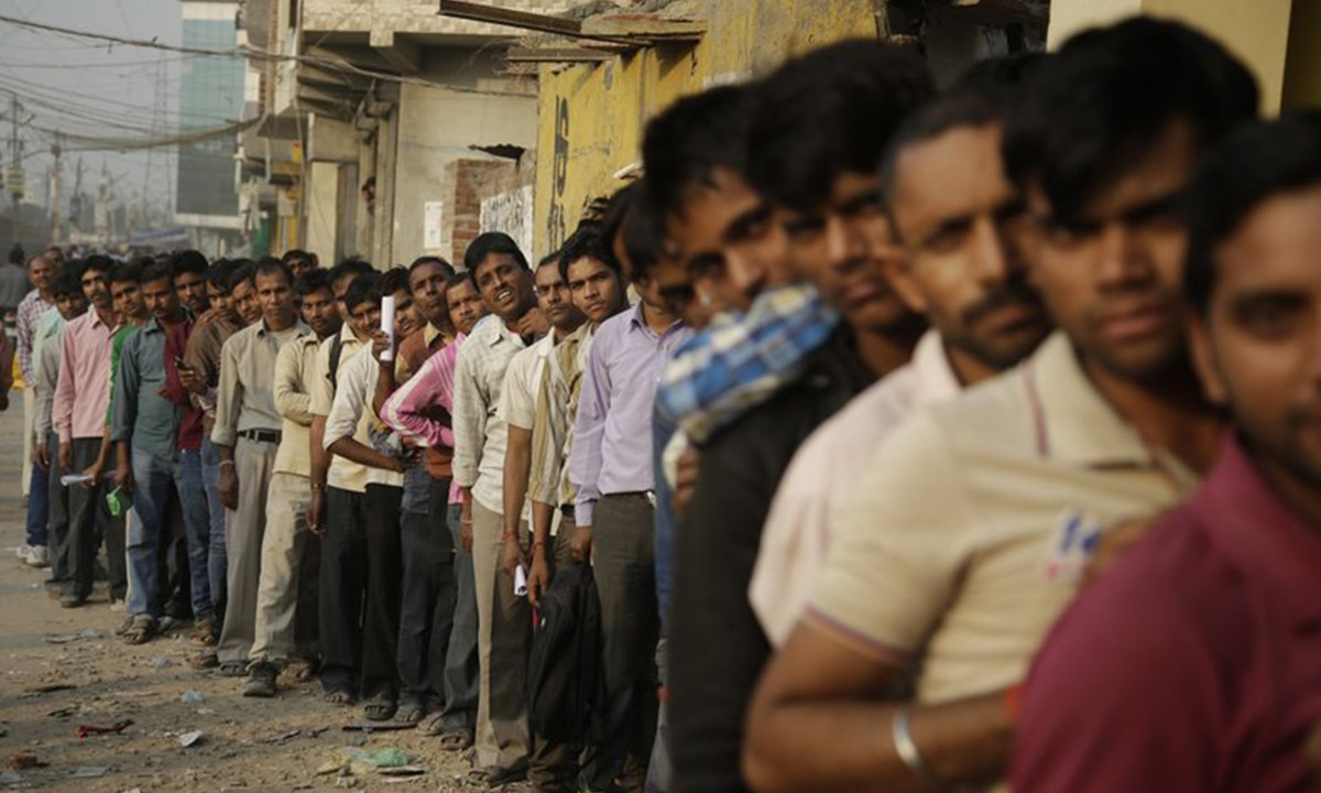 Indians stand in a queue to deposit and exchange discontinued currency notes outside a bank in New Delhi, India | AP