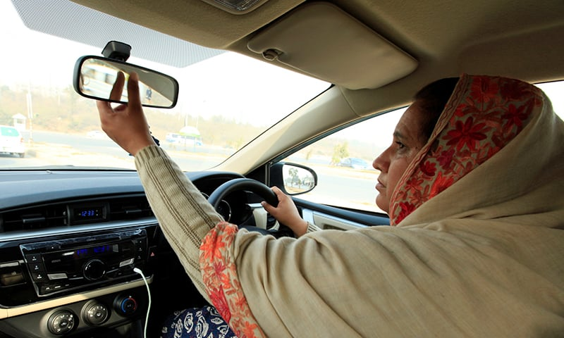 "Yasmin Perveen, one of the pioneer women ""captains"" of Careem, adjusts back mirror while driving her car in Islamabad on Dec 7. ─ Reuters"