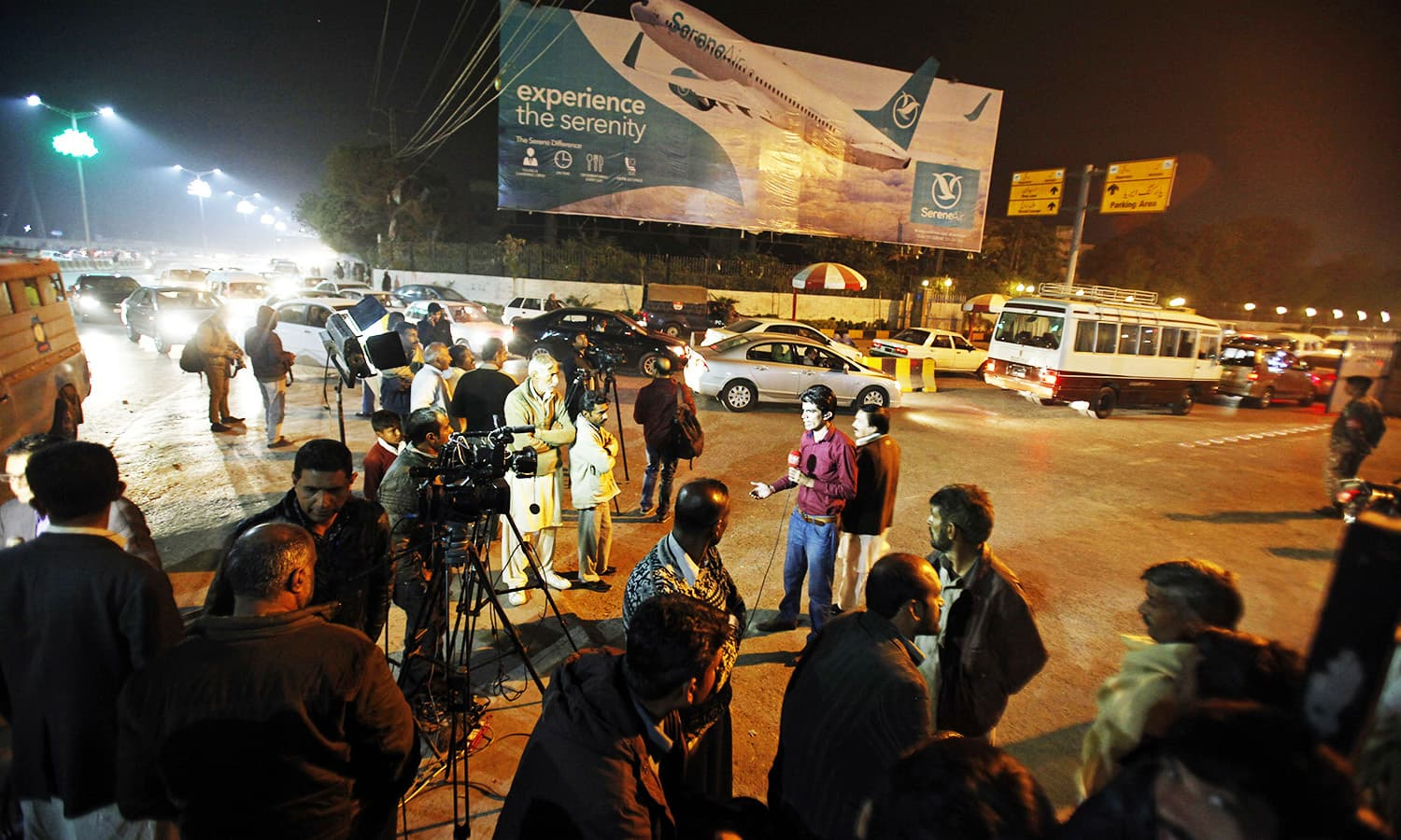 Pakistani media and residents gather at Benazir Bhutto International Airport following the crash. -AP