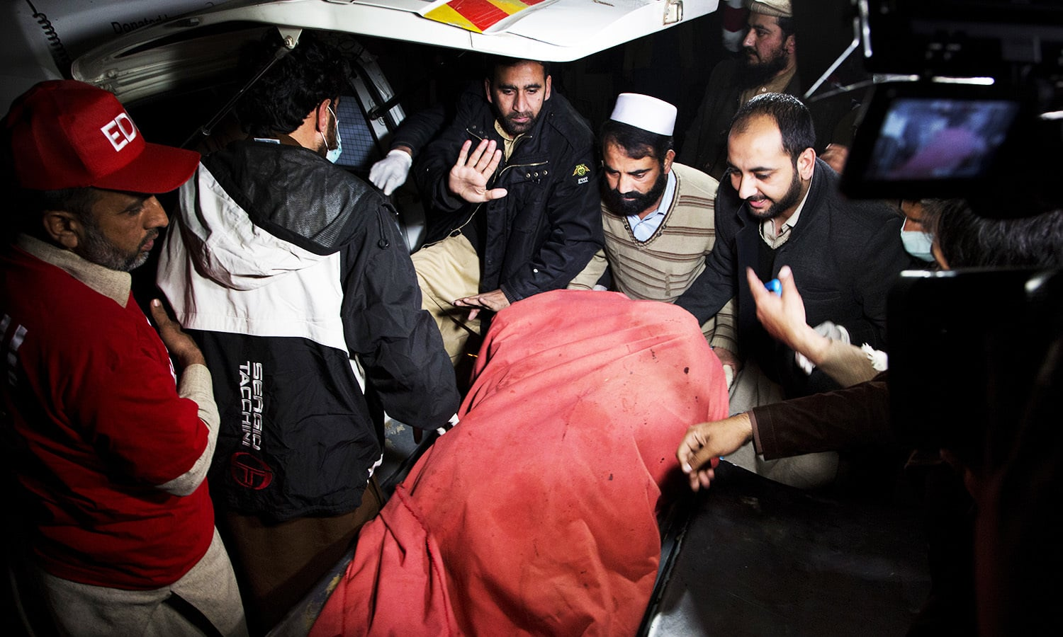 Pakistani volunteers move remains of plane crash victims to a mortuary at a hospital in Abbottabad. -AP