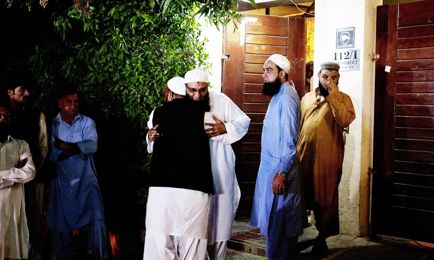 Relatives and friends of Pakistani singer-turned Islamic preacher Junaid Jamshed, comfort each other outside his home. -AP