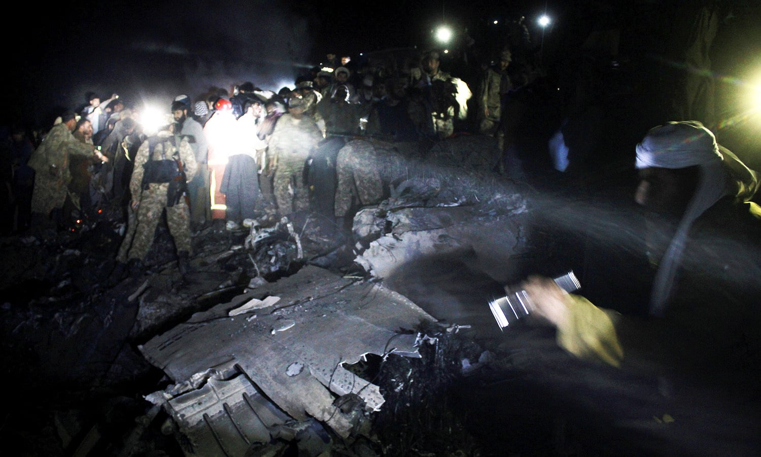 Pakistan Army troops and rescue workers search for bodies at the site of a plane crash. -AP