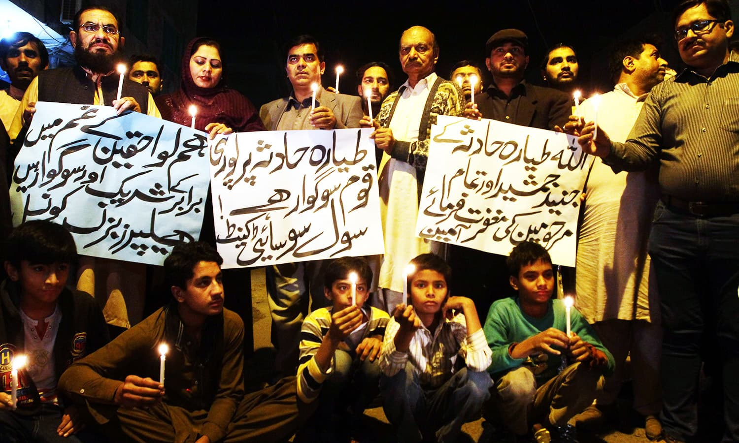 Members of a civil society group hold candles during a vigil for the victims of a plane crash in Multan. -AP