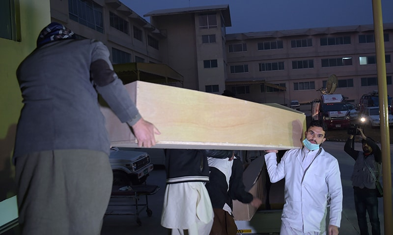 Hospital workers unload coffins for air crash victims of Pakistan International Airlines (PIA) Flight PK-661. ─ AFP