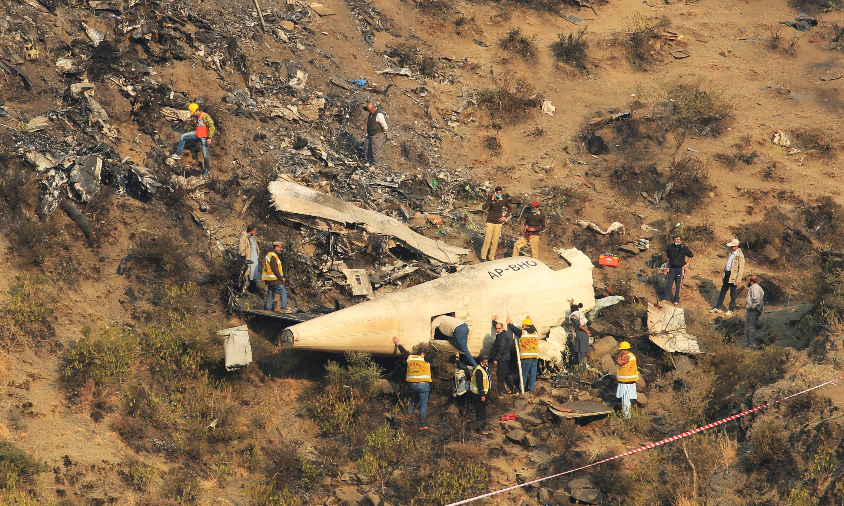 Rescue workers survey the site of a plane crashed a day earlier. — Reuters