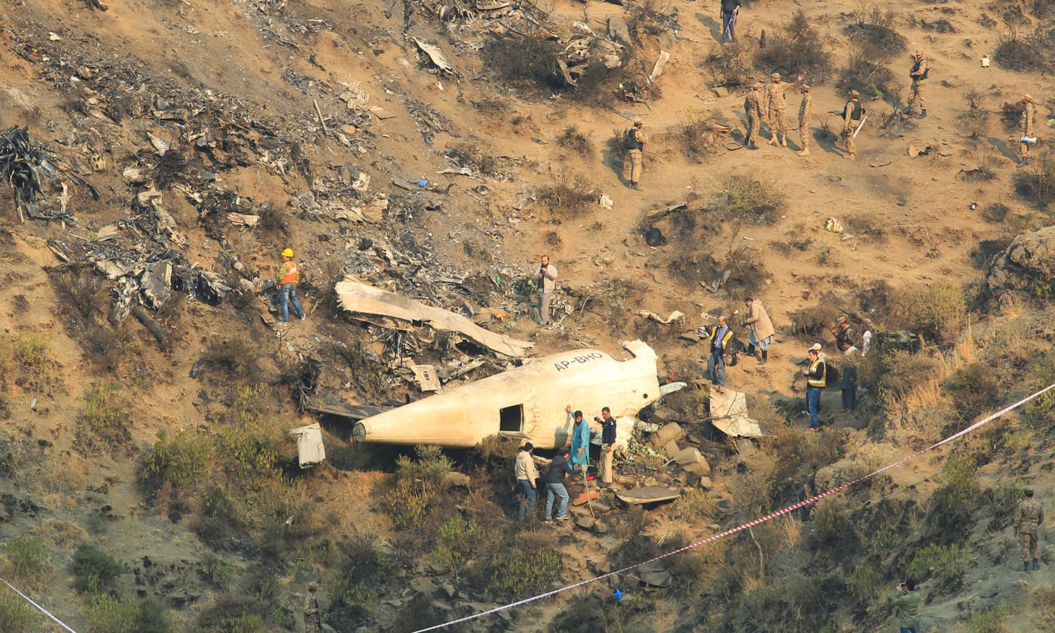 Rescue workers survey the site of the plane crash. ─Reuters