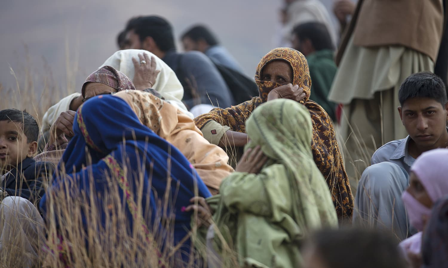 Pakistani villagers look upon the wreckage of the crash. ─AP
