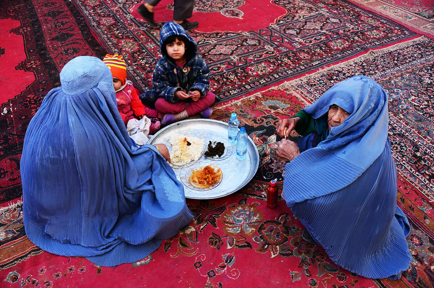 Afghan women and children eat during celebrations marking the birth anniversary of the Prophet Muhammad (PBUH).—AFP