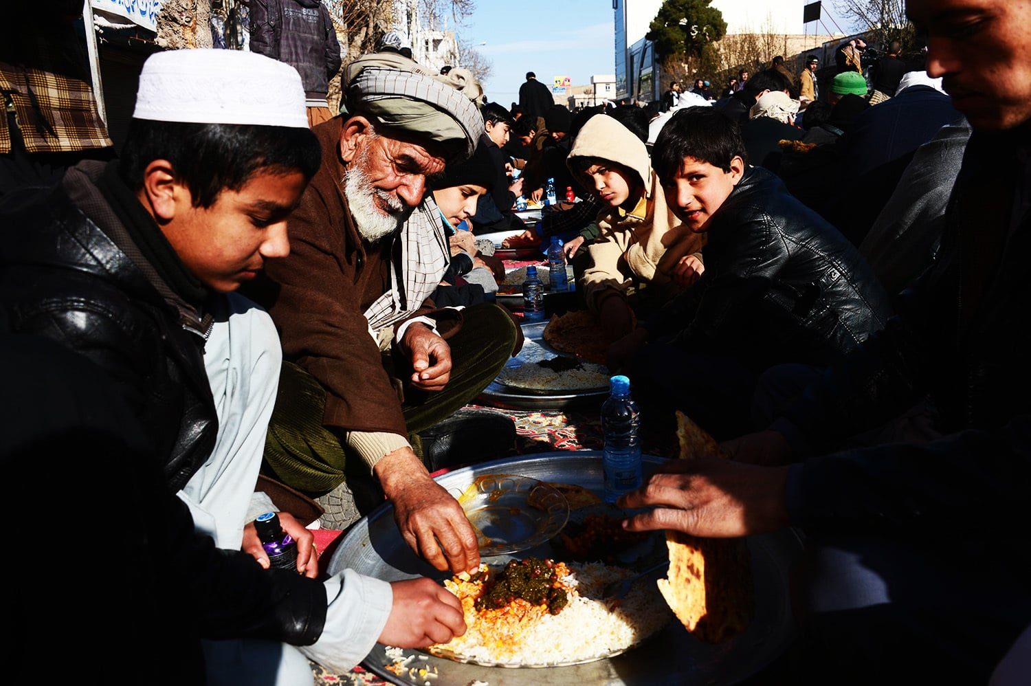 Afghan men and boys eat during celebrations marking the birth anniversary of the Prophet Muhammad (PBUH).—AFP