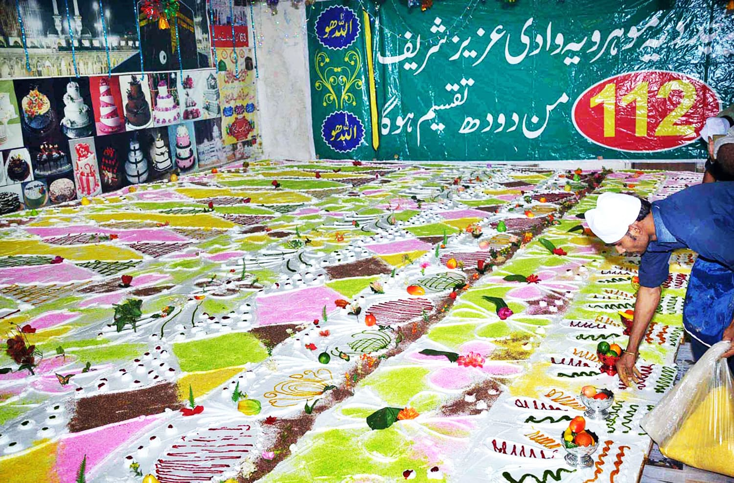 A worker is busy in preparing a 2520kg cake at the shrine of Hazrat Pir Sufi Muhammad on the eve of Eid Milad Un Nabi (PBHU).—APP