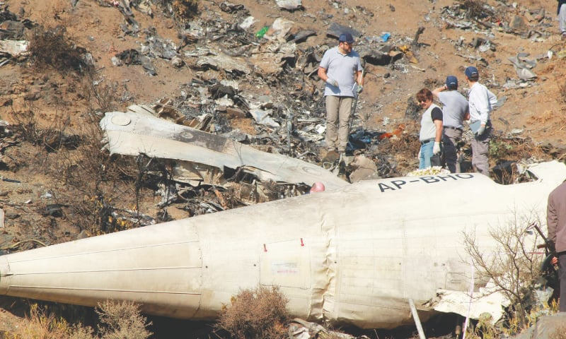 Foreign experts examine the wreckage of the plane.— AFP
