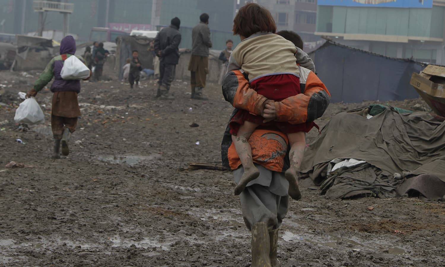 A displaced Afghan child carries another child on his back after picking up food rations from a truck organised by the World Food Program in Kabul. — AP