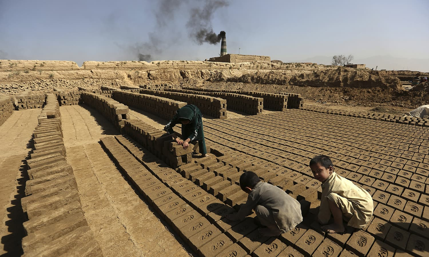 Afghan children help their father's work at a local brick factory on the outskirts of Kabul. — AP