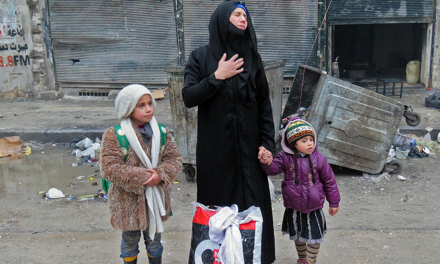 A Syrian woman, fleeing violence in the restive Bustan al-Qasr neighbourhood, reacts as she stands with her children in Aleppo's Fardos neighbourhood. ─AFP
