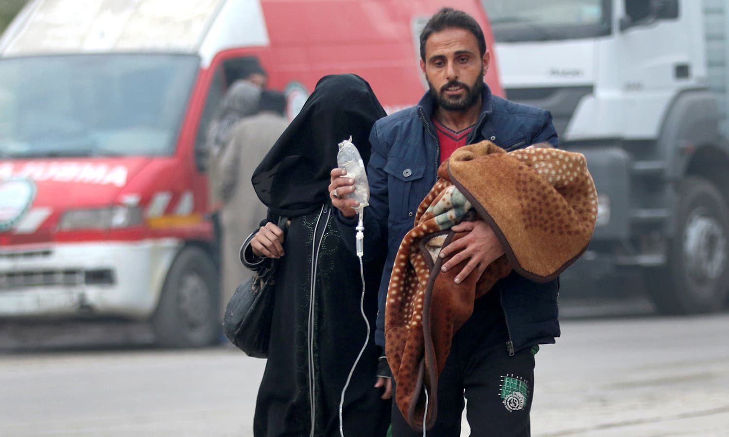 A man carries a child with an IV drip as he flees deeper into the remaining rebel-held areas of Aleppo. ─Reuters
