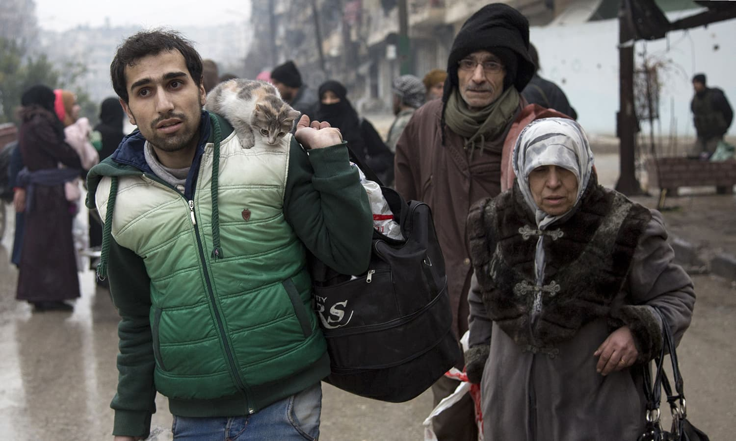Syrians leave a rebel-held area of Aleppo towards the government-held side. ─AFP