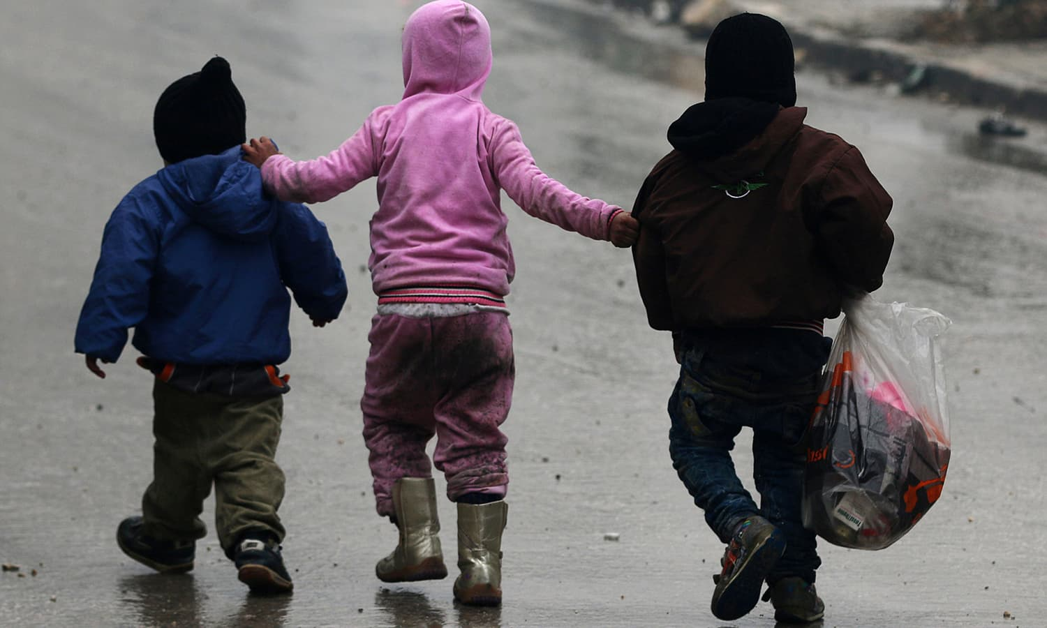 Children walk together as they flee deeper into the remaining rebel-held areas of Aleppo. ─Reuters