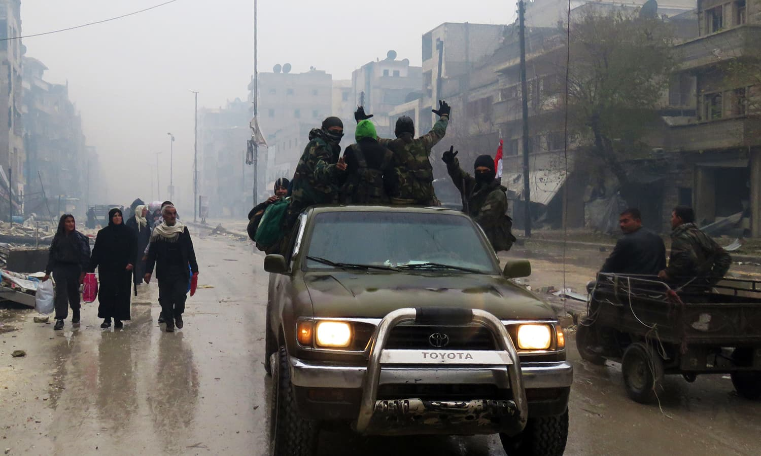Syrian pro-regime fighters, gesture as they drive past resident fleeing violence in the restive Bustan al-Qasr neighbourhood, in Aleppo's Fardos neighbourhood on December 13, 2016, after regime troops retook the area from rebel fighters. ─ AFP