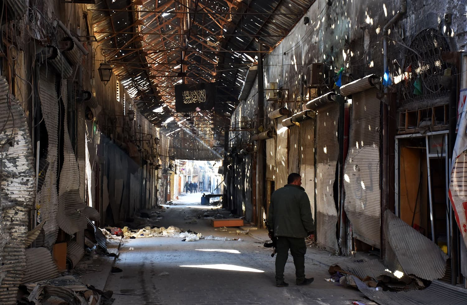 This file photo taken on Dec 9, 2016 shows a Syrian pro-government fighter walking past closed shops in the Bab al-Nasr district of Aleppo's Old City. ─ AFP