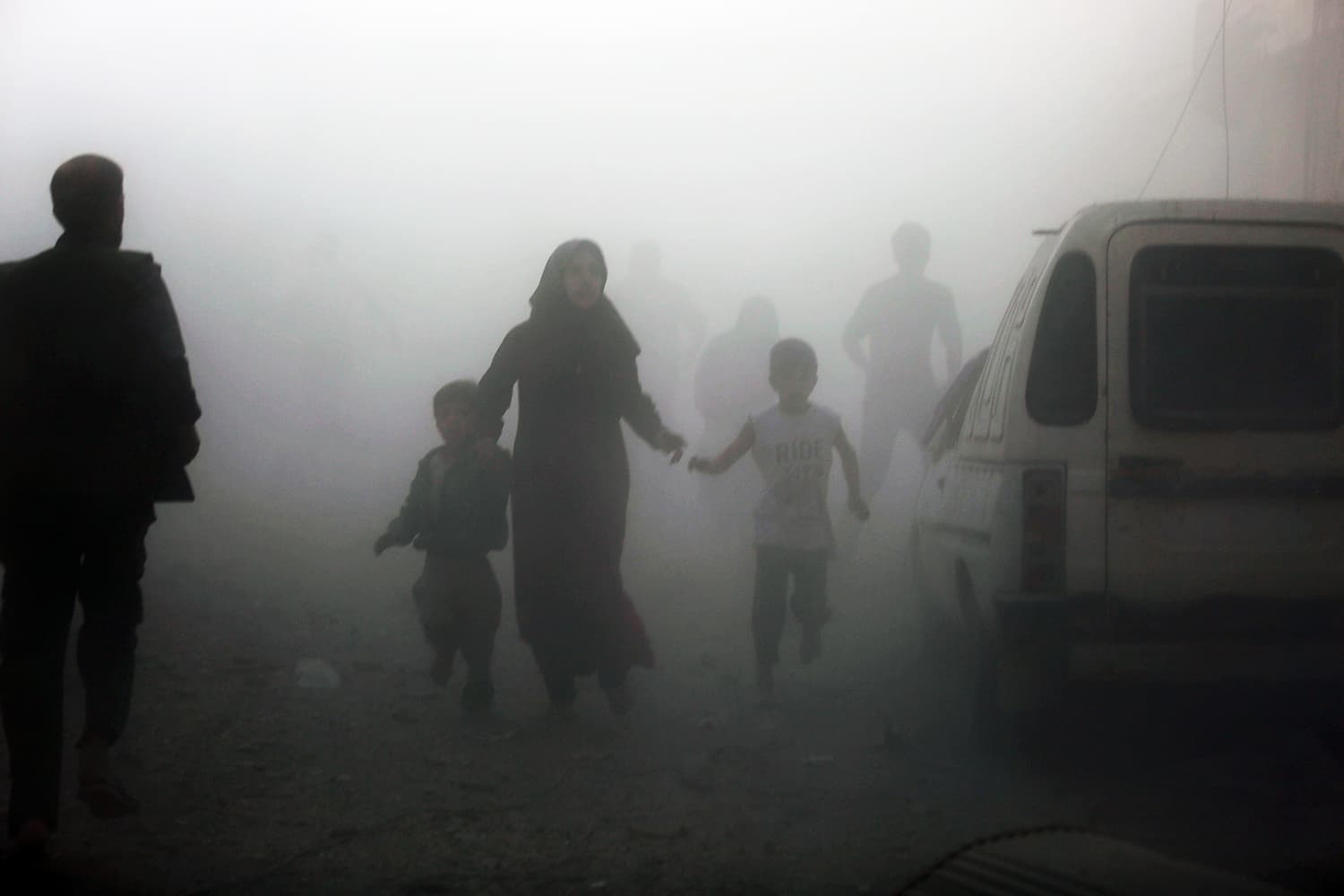 Syrians emerge from a dust cloud following a reported airstrike on Kafr Batna, in the rebel-held Eastern Ghouta area, on the outskirts of the capital Damascus, on September 30, 2016. ─ AFP