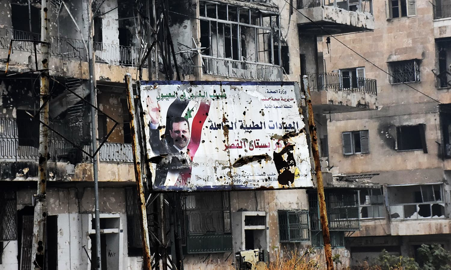 A general view shows a poster of Assad in Aleppo's Bustan al-Qasr neighbourhood after Syrian pro-government forces captured the area in the eastern part of the war torn city on December 13, 2016. ─ AFP
