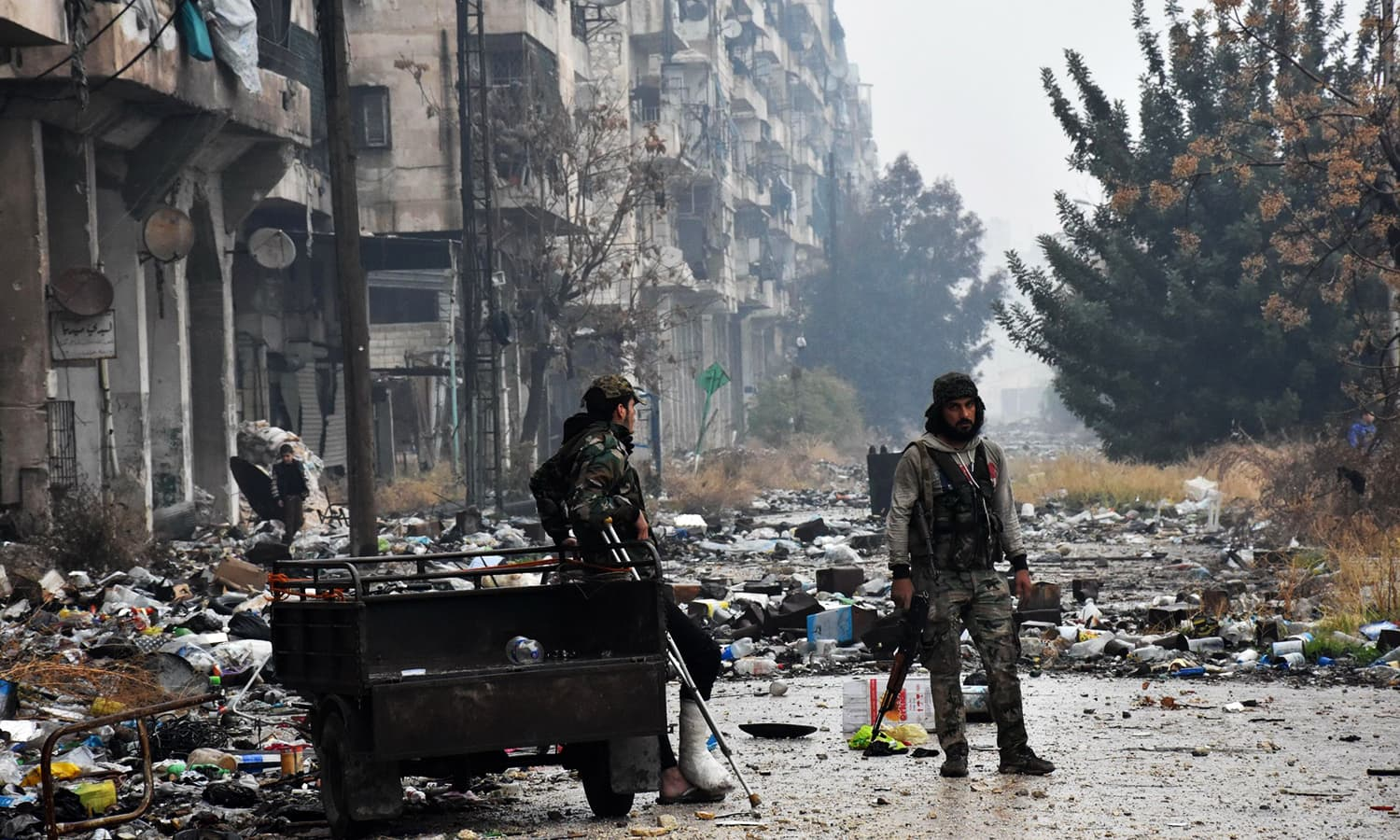 Syrian pro-government forces walk in Aleppo's Bustan al-Qasr neighbourhood after they captured the area in the eastern part of the war torn city on December 13, 2016. ─ AFP