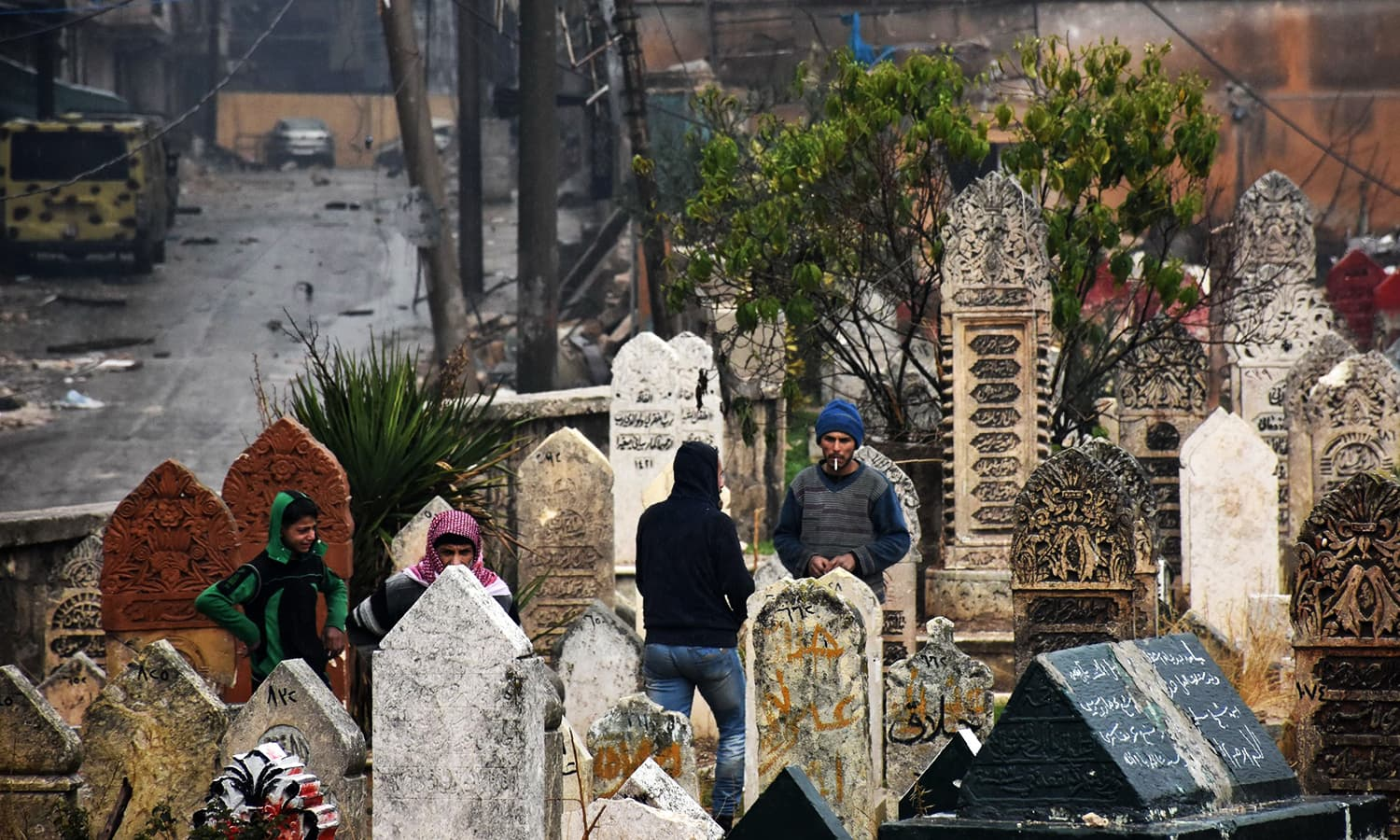 Syrian residents stand in a graveyard in Aleppo's Al-Kalasseh neighbourhood that was newly captured by pro-governments forces in the eastern part of the war torn city on December 13, 2016. ─ AFP