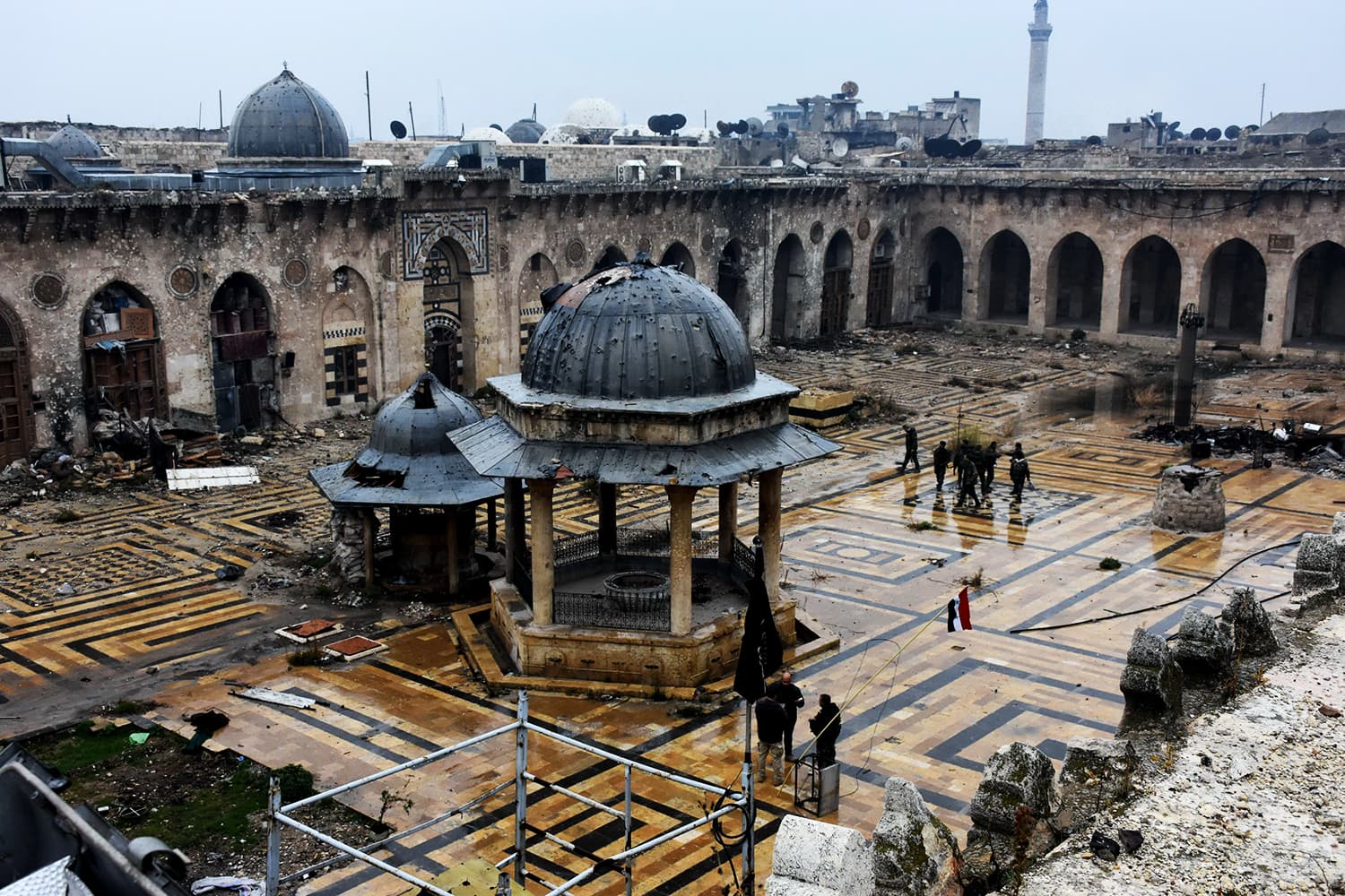 Syrian pro-government forces walk in the ancient Umayyad mosque in the old city of Aleppo after they captured the area in the eastern part of the war torn city on December 13, 2016. ─ AFP