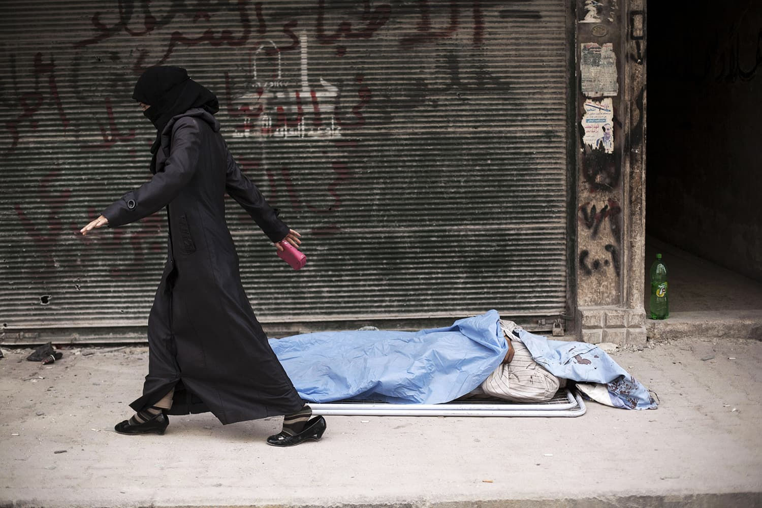 A Syrian woman walks past a body in front of Dar El Shifa Hospital, Aleppo, Syria, Wednesday, Oct. 10, 2012. ─ AP/File